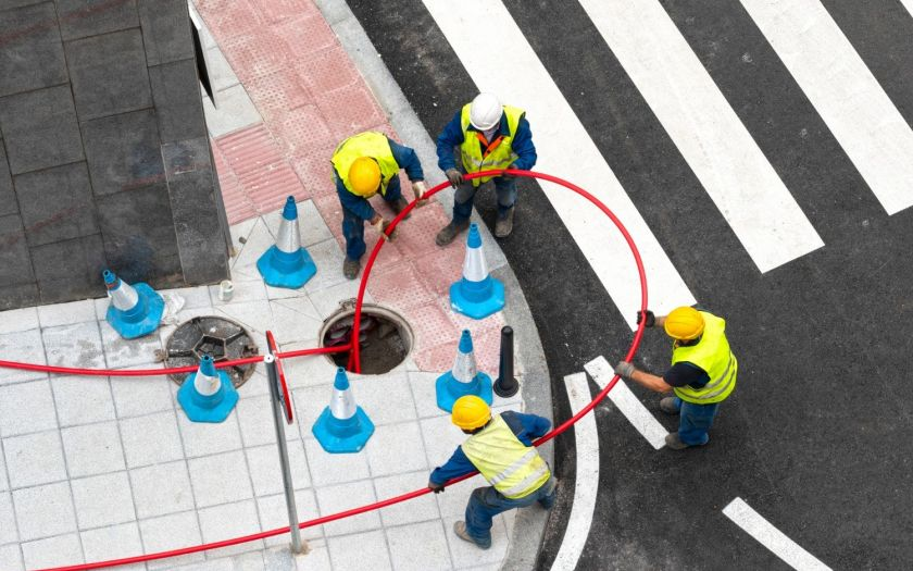 | Workers Pulling Cable Across Pipes To Supply Energy To A Neighbourhood Web