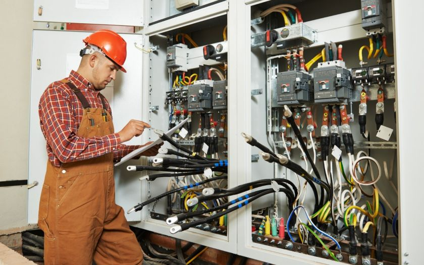   Electrician In Front Of Switchboard Holding Specification Web